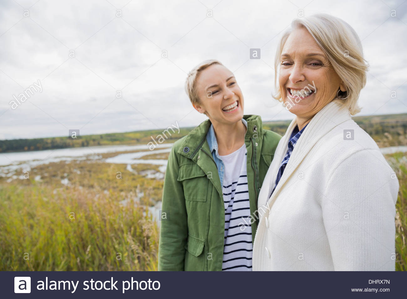 Cheerful mother and daughter at lakeshore - Stock Image