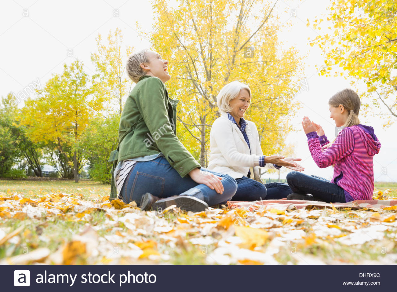 Three generation family playing clapping game in park - Stock Image