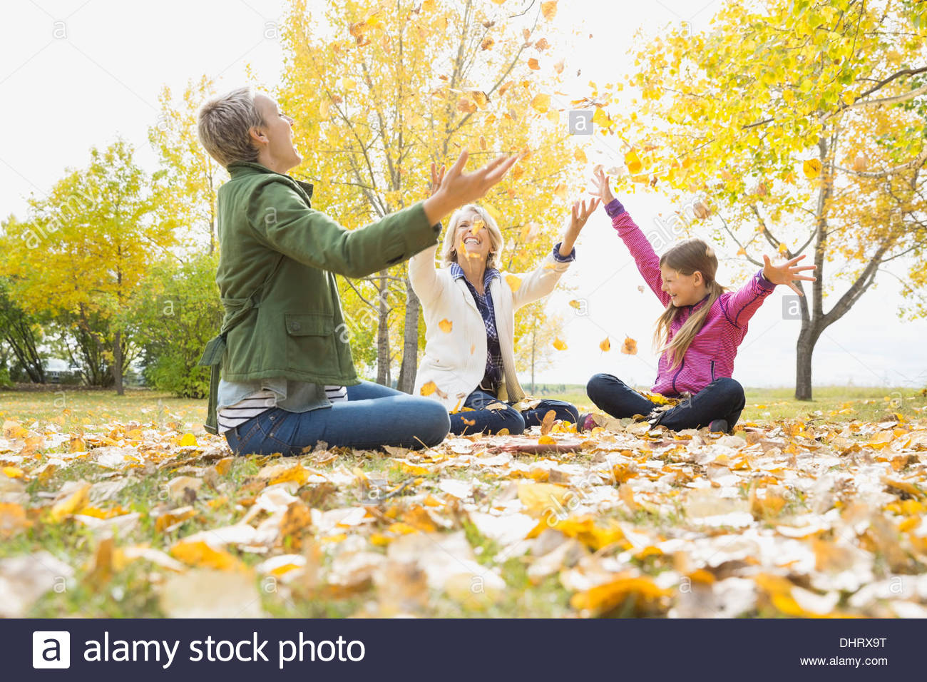 Female family members throwing autumn leaves in park Stock Photo