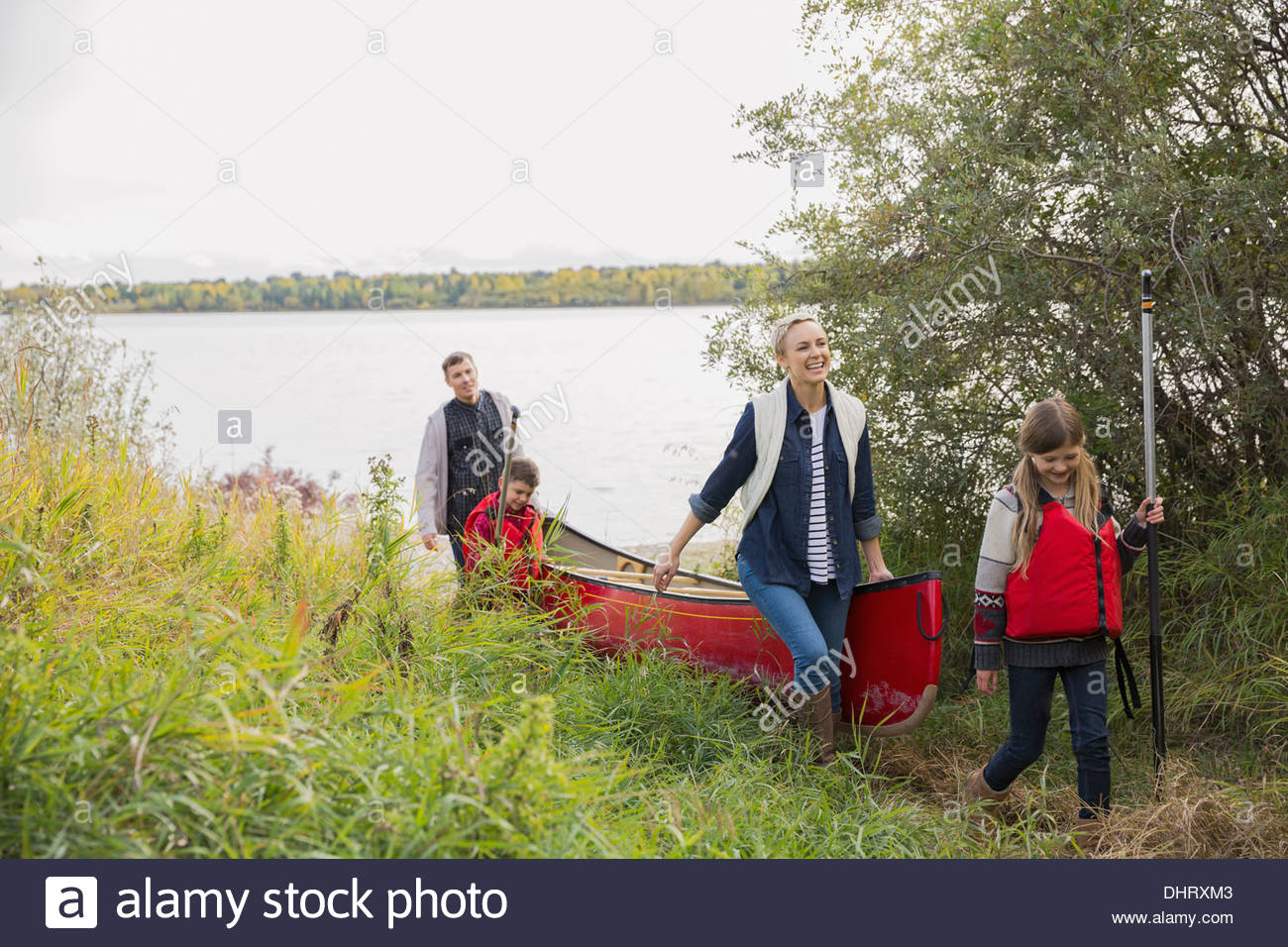 Family carrying canoe by lakeshore - Stock Image