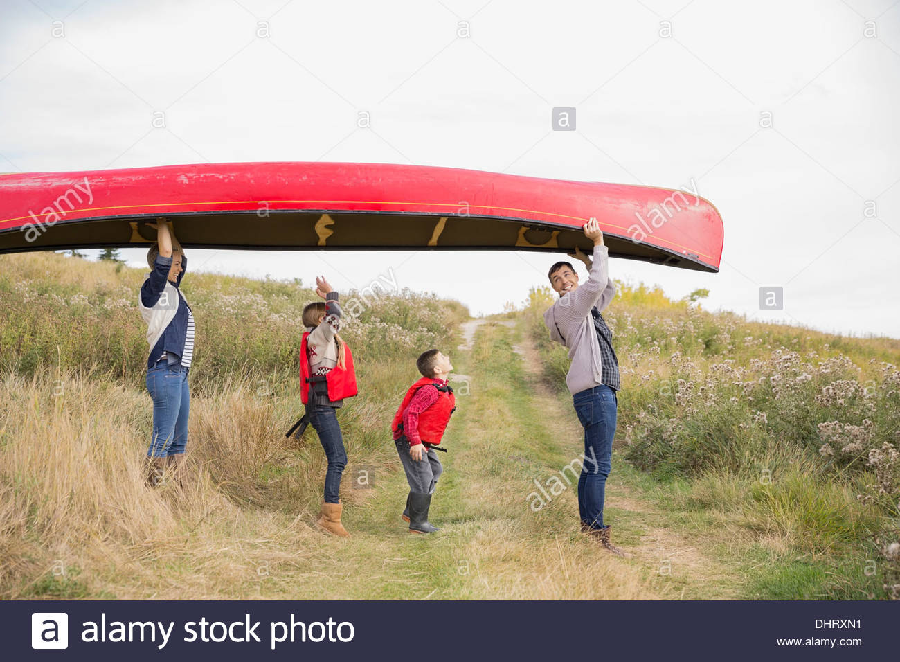 Profile shot of family carrying canoe - Stock Image