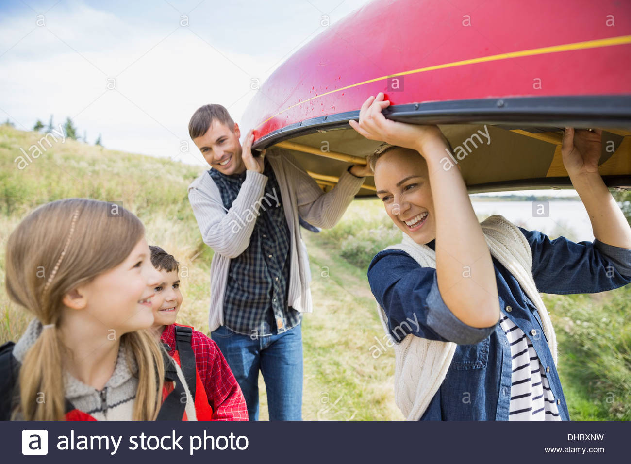 Family carrying canoe to lakeshore - Stock Image
