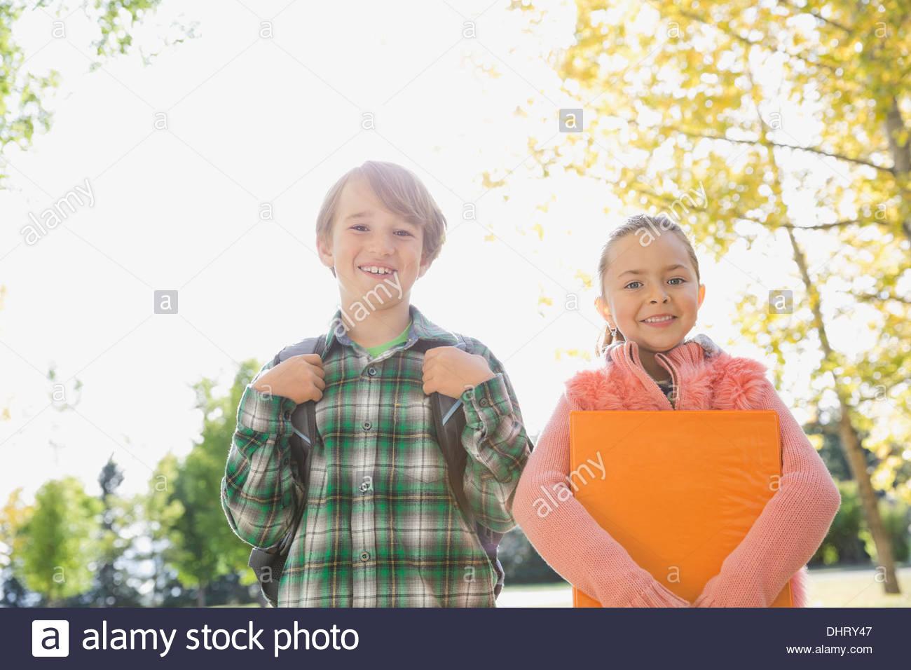 Portrait of happy school children outdoors - Stock Image
