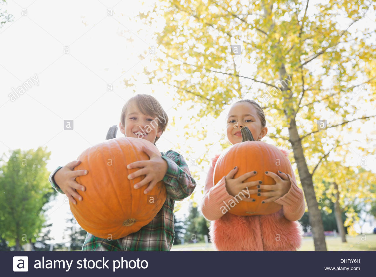 Portrait of kids carrying pumpkins - Stock Image