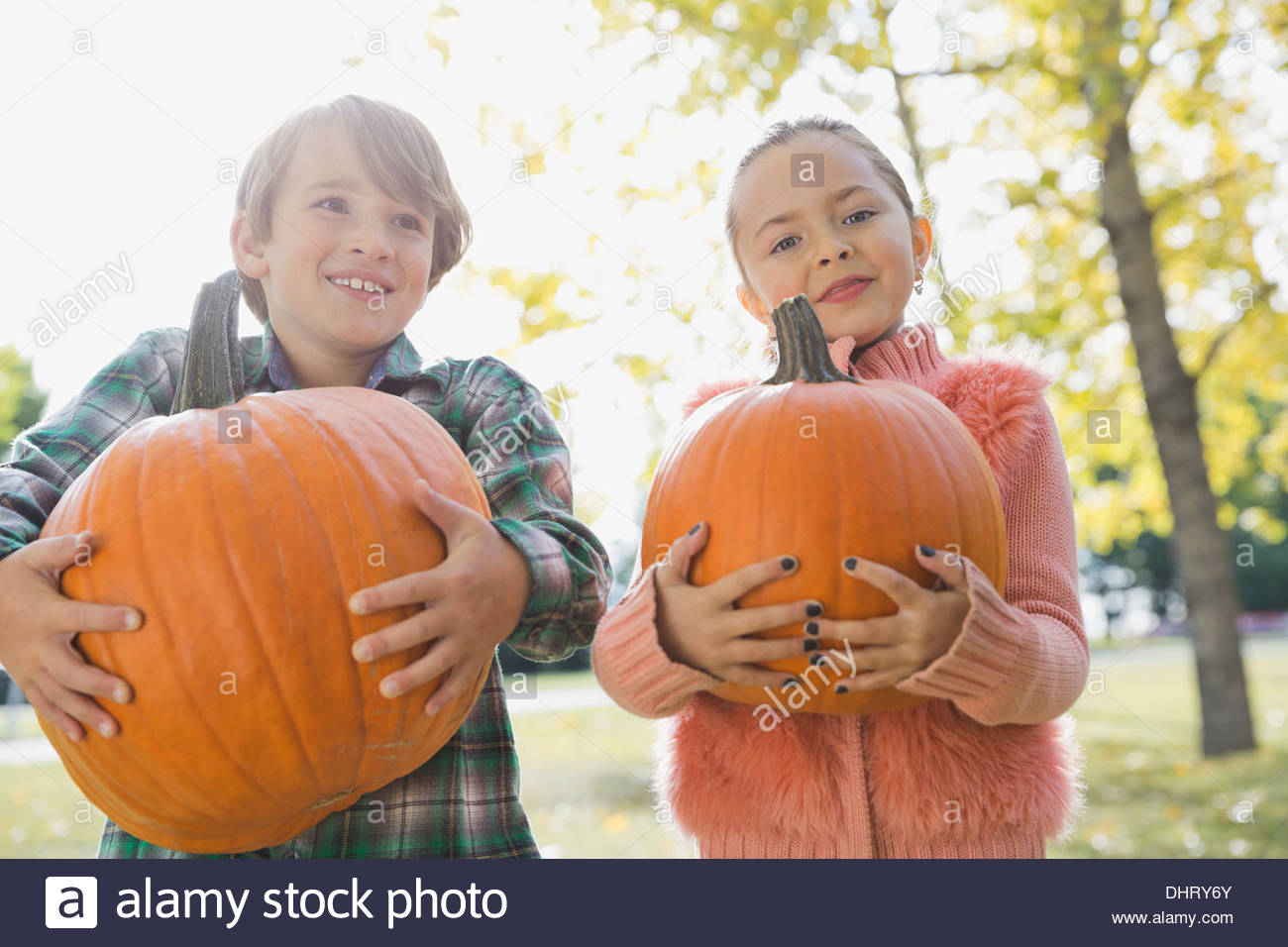 Kids carrying pumpkins - Stock Image