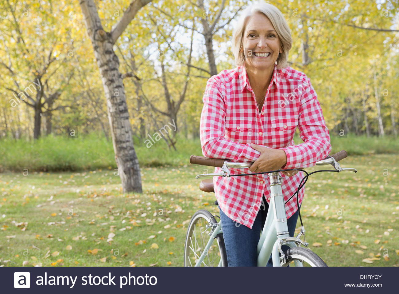 Smiling woman leaning on bicycle - Stock Image