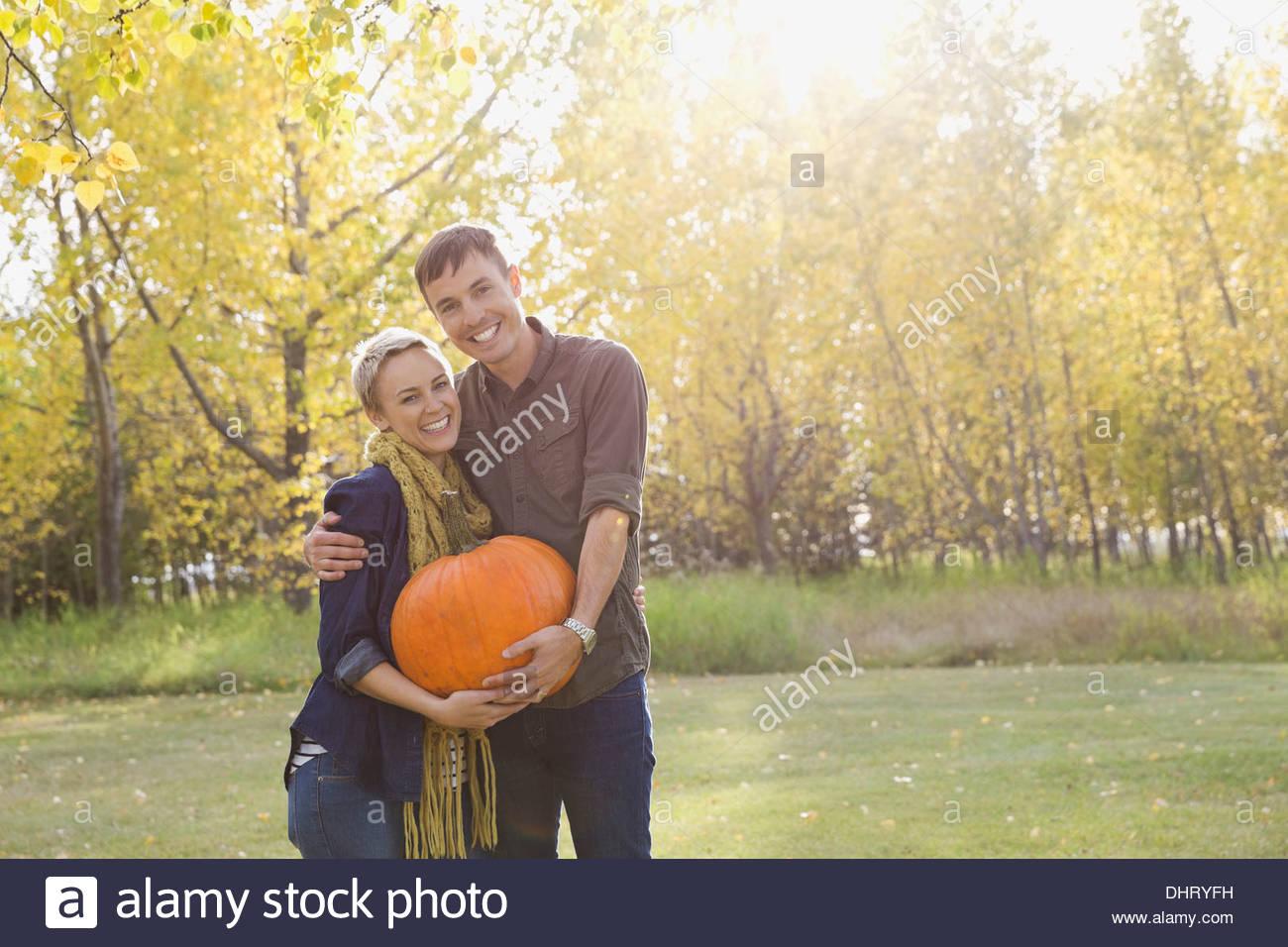 Happy couple holding pumpkin - Stock Image