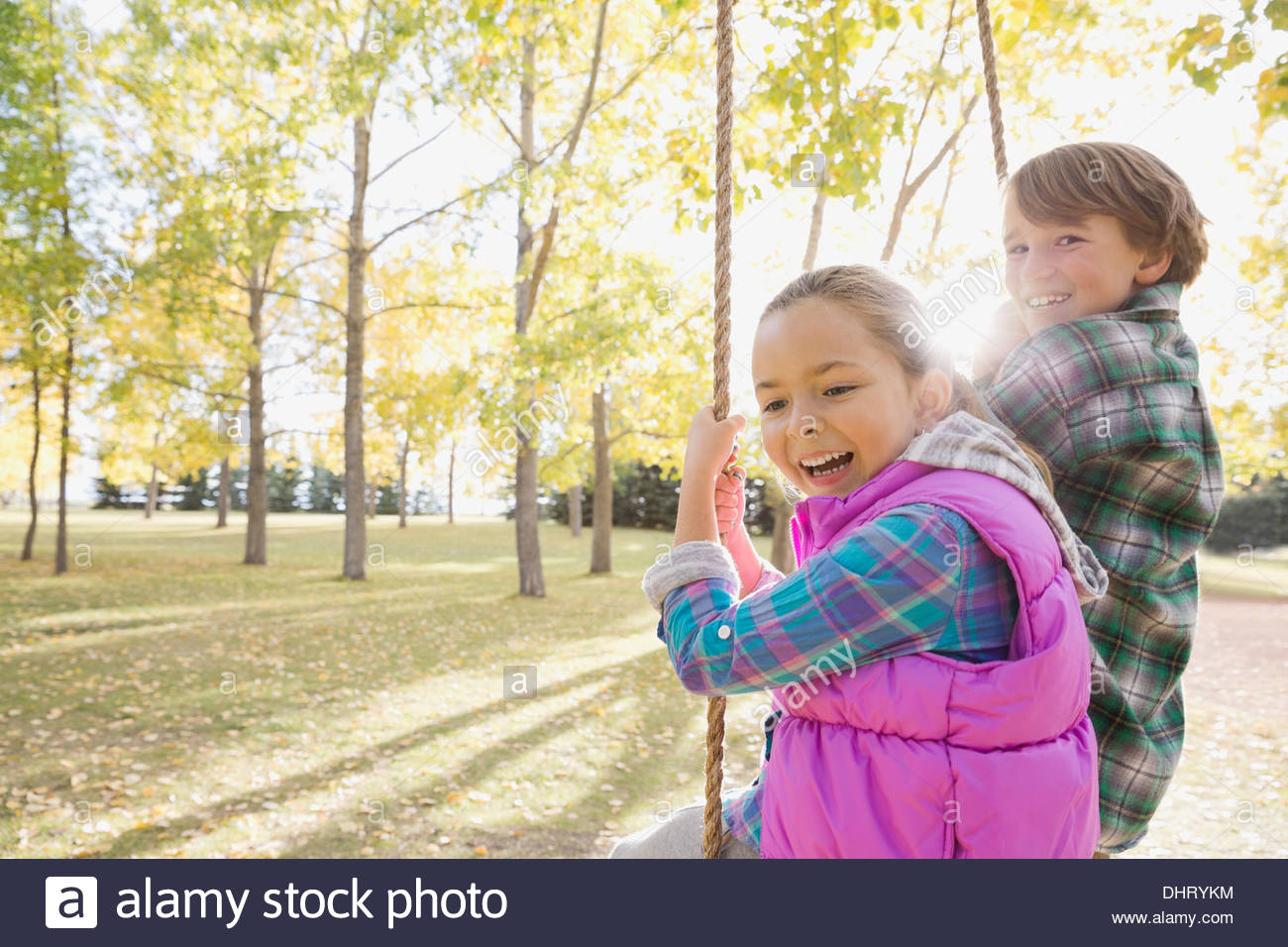 Siblings swinging at park - Stock Image
