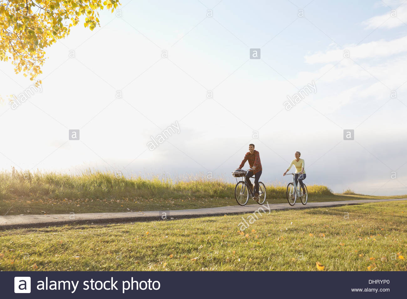 Full length of couple cycling on country road - Stock Image