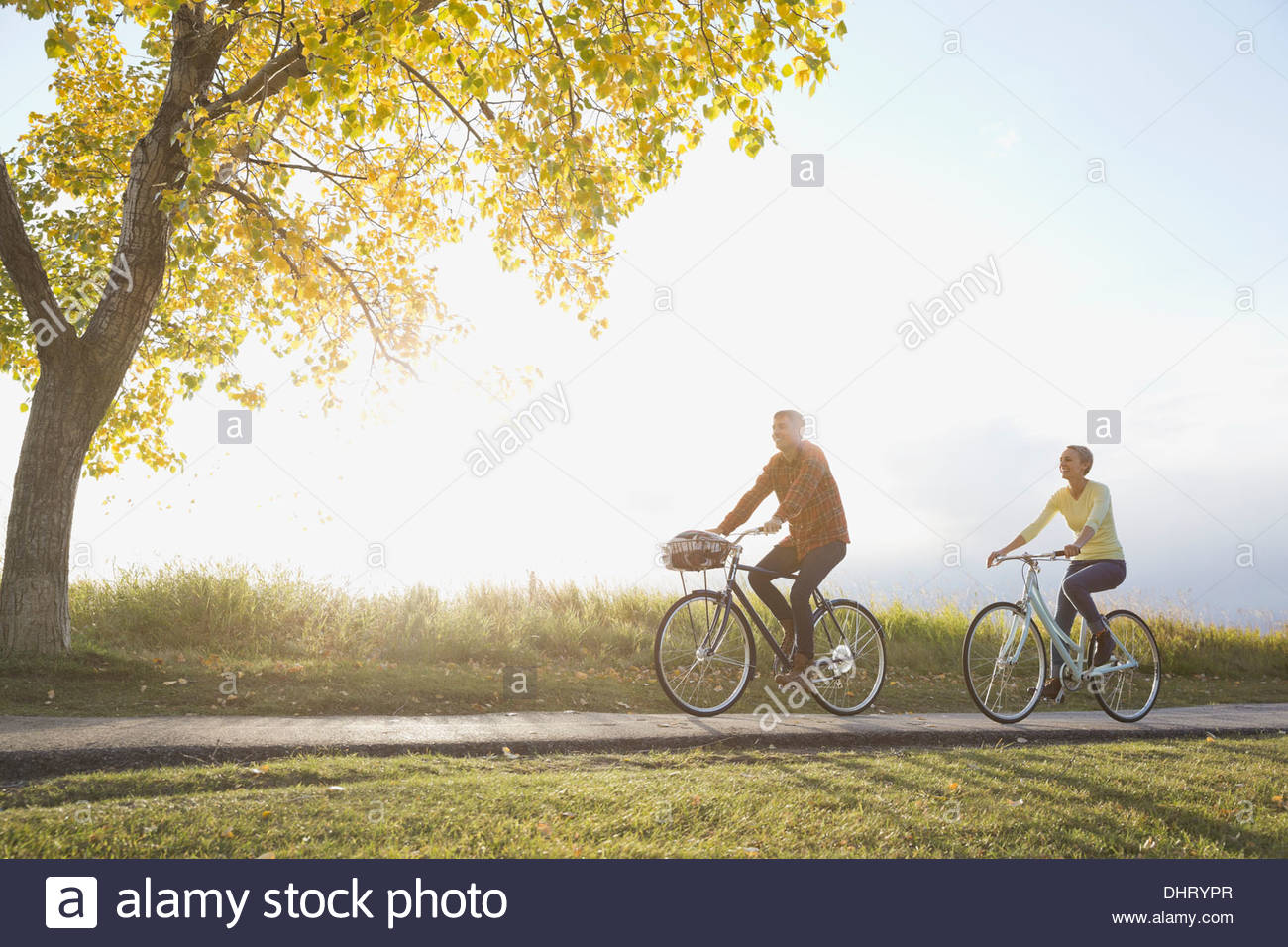 Couple cycling on country road - Stock Image