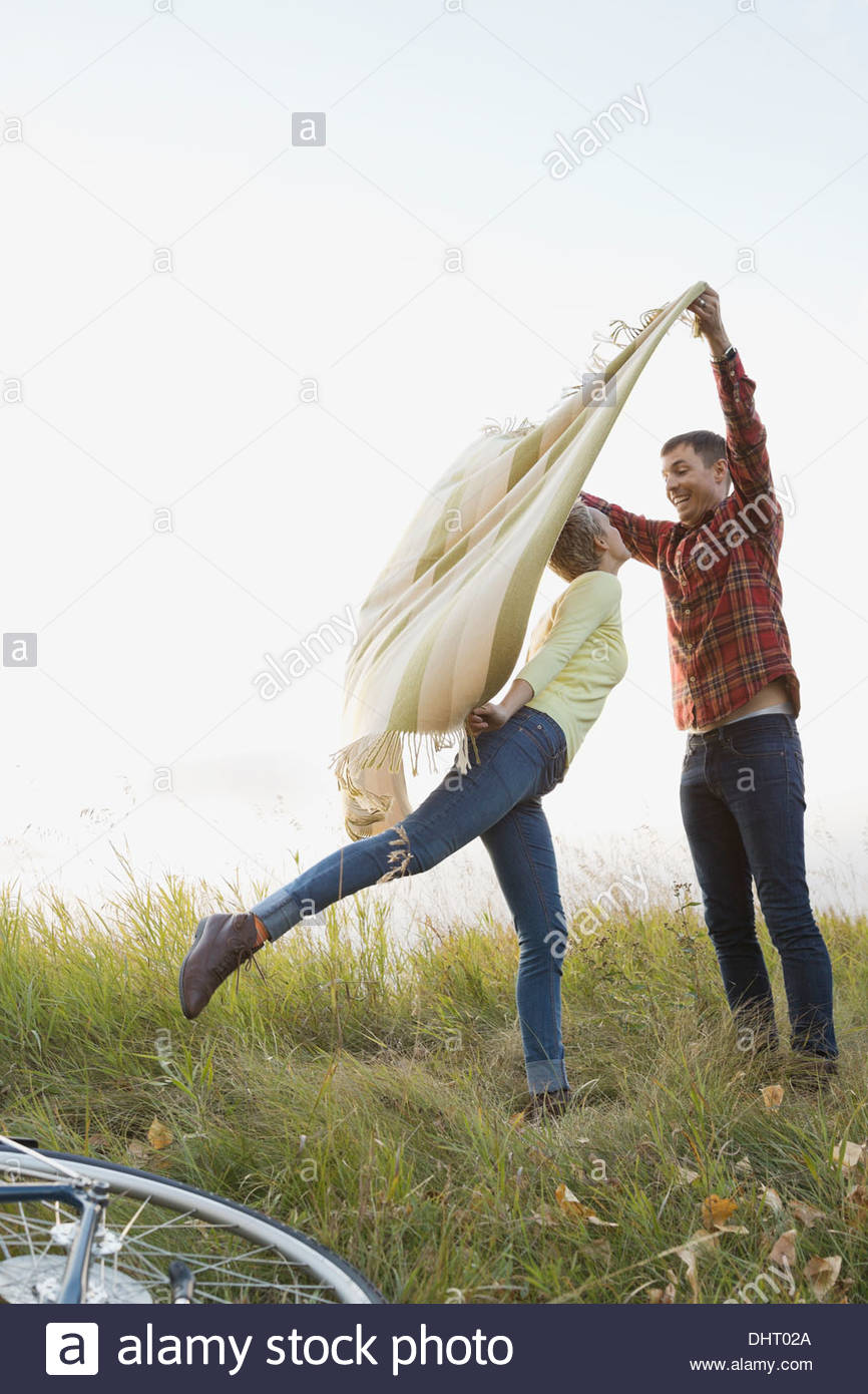 Playful couple spreading out blanket at field - Stock Image
