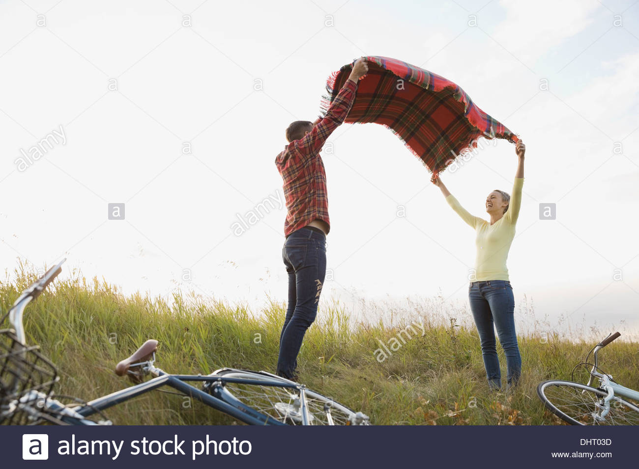 Couple spreading out blanket at field - Stock Image