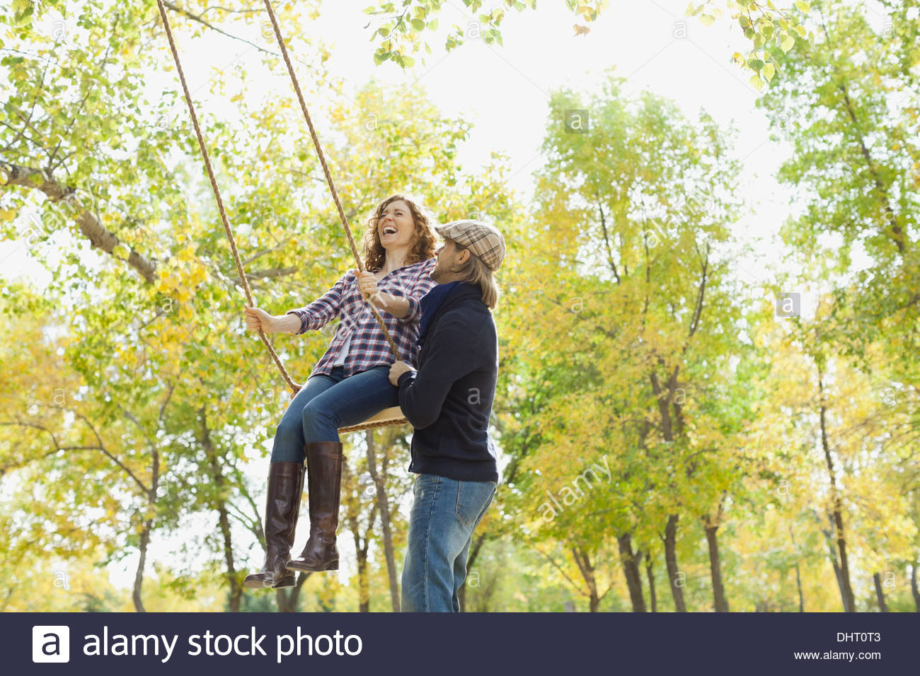 Mid adult man pushing woman on swing at park during autumn - Stock Image
