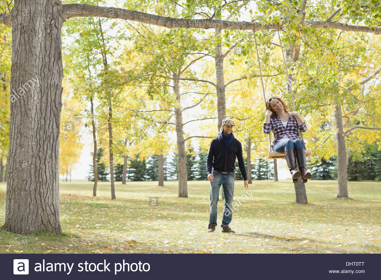 Full length of happy man looking at woman swinging in park - Stock Image