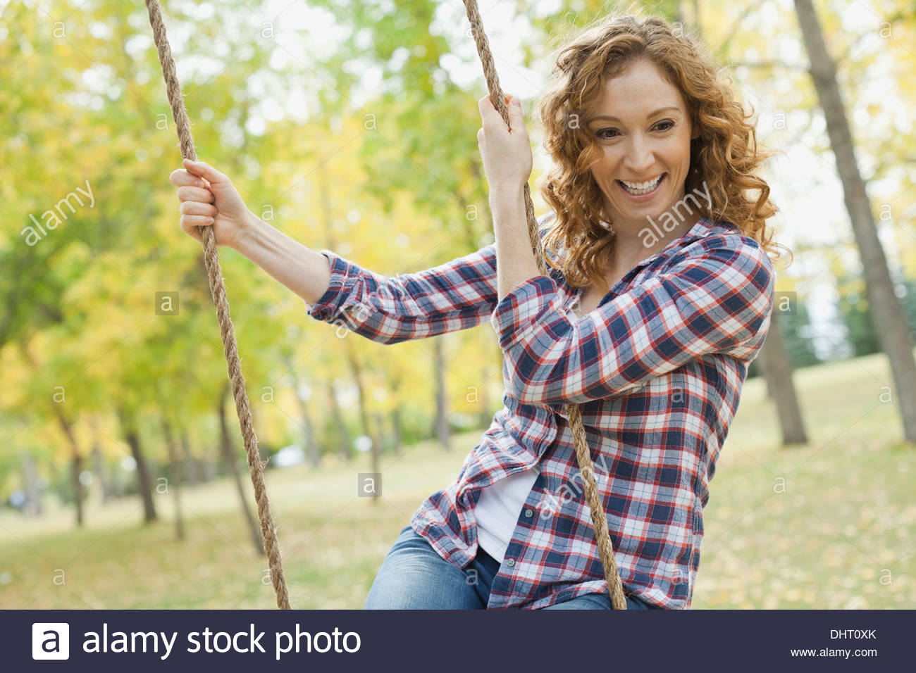 Happy mid adult woman swinging at park - Stock Image