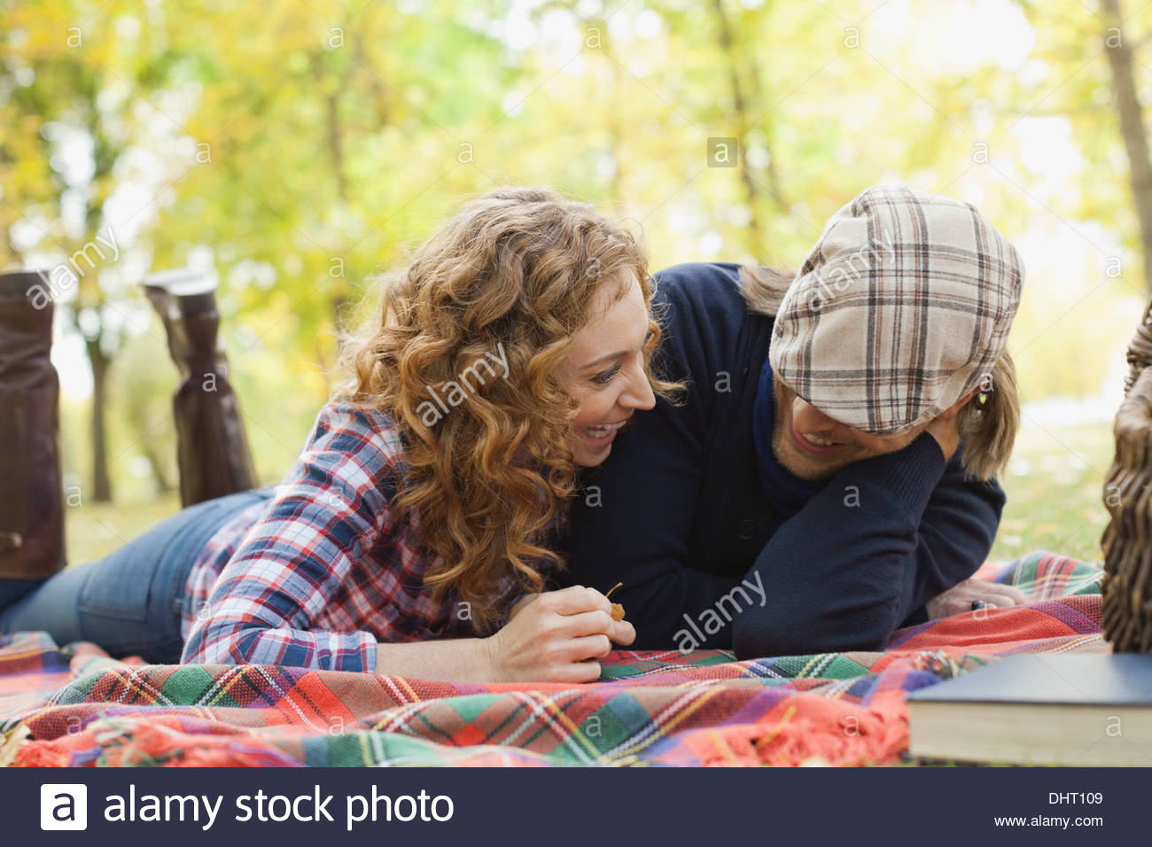 Happy mid adult couple lying on blanket at park - Stock Image