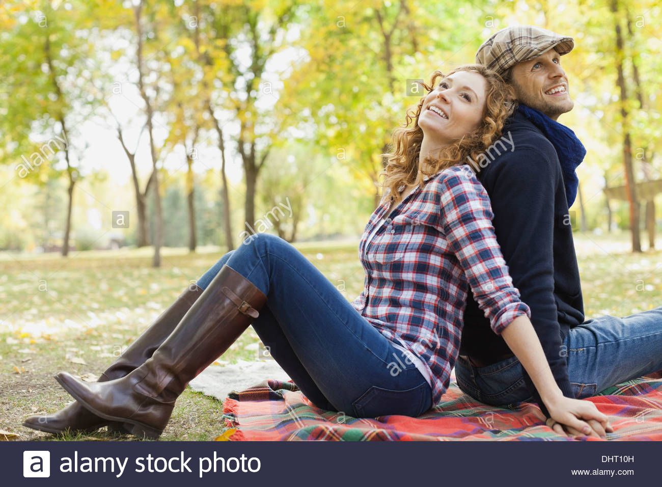 Happy mid adult couple sitting at park during autumn - Stock Image