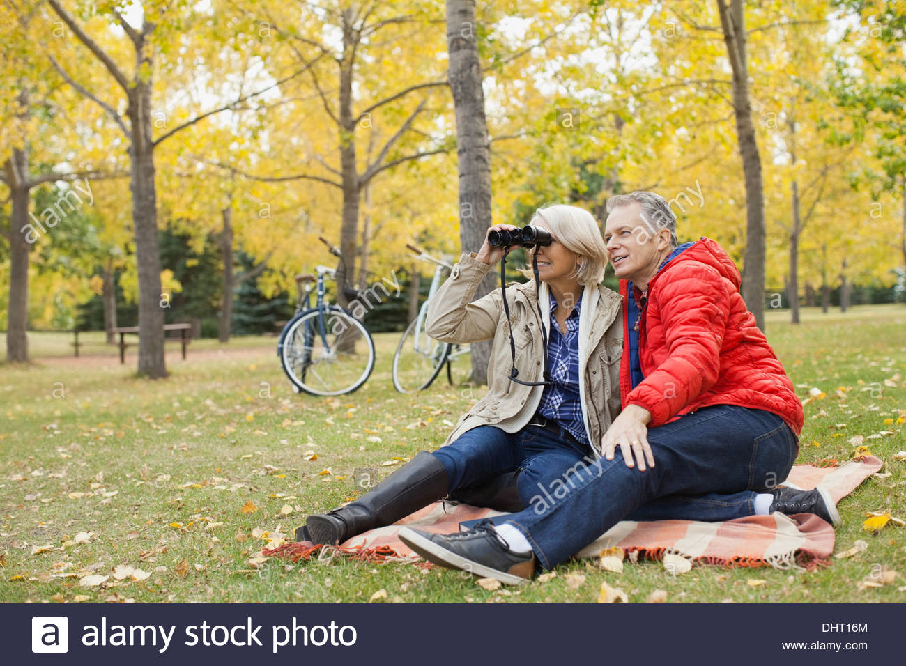 Full length of mature man with woman looking through binoculars at park - Stock Image
