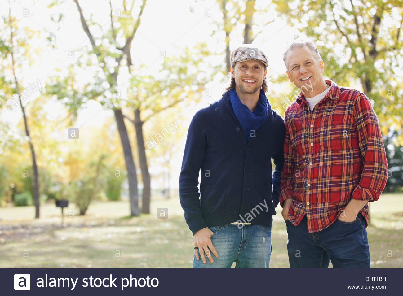 Portrait of happy mid adult man with father at park during autumn - Stock Image