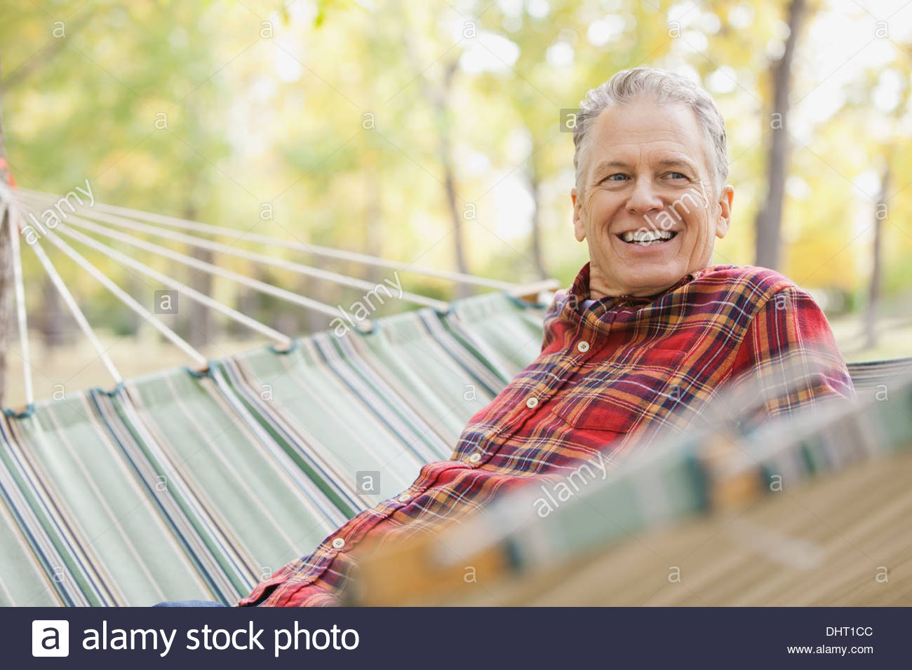 Happy mature man sitting in hammock at park - Stock Image