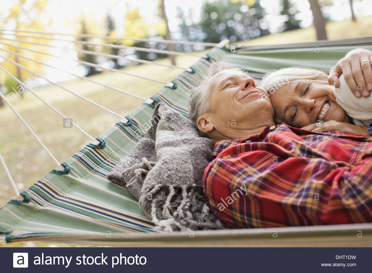 Loving mature couple lying in hammock at park - Stock Image