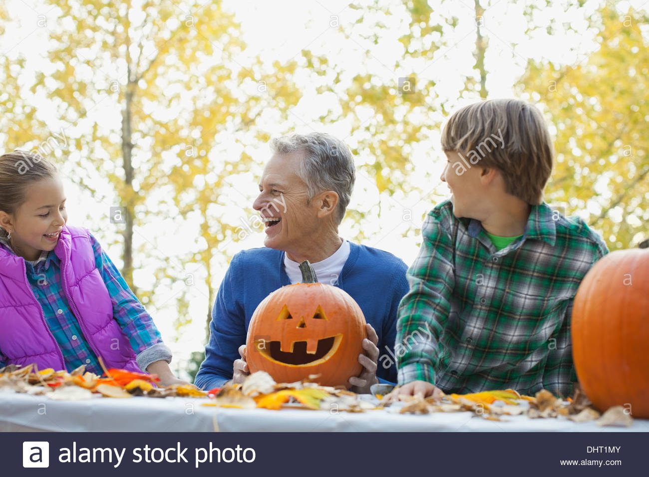 Happy grandfather and boy with jack o lanterns looking at girl in park - Stock Image