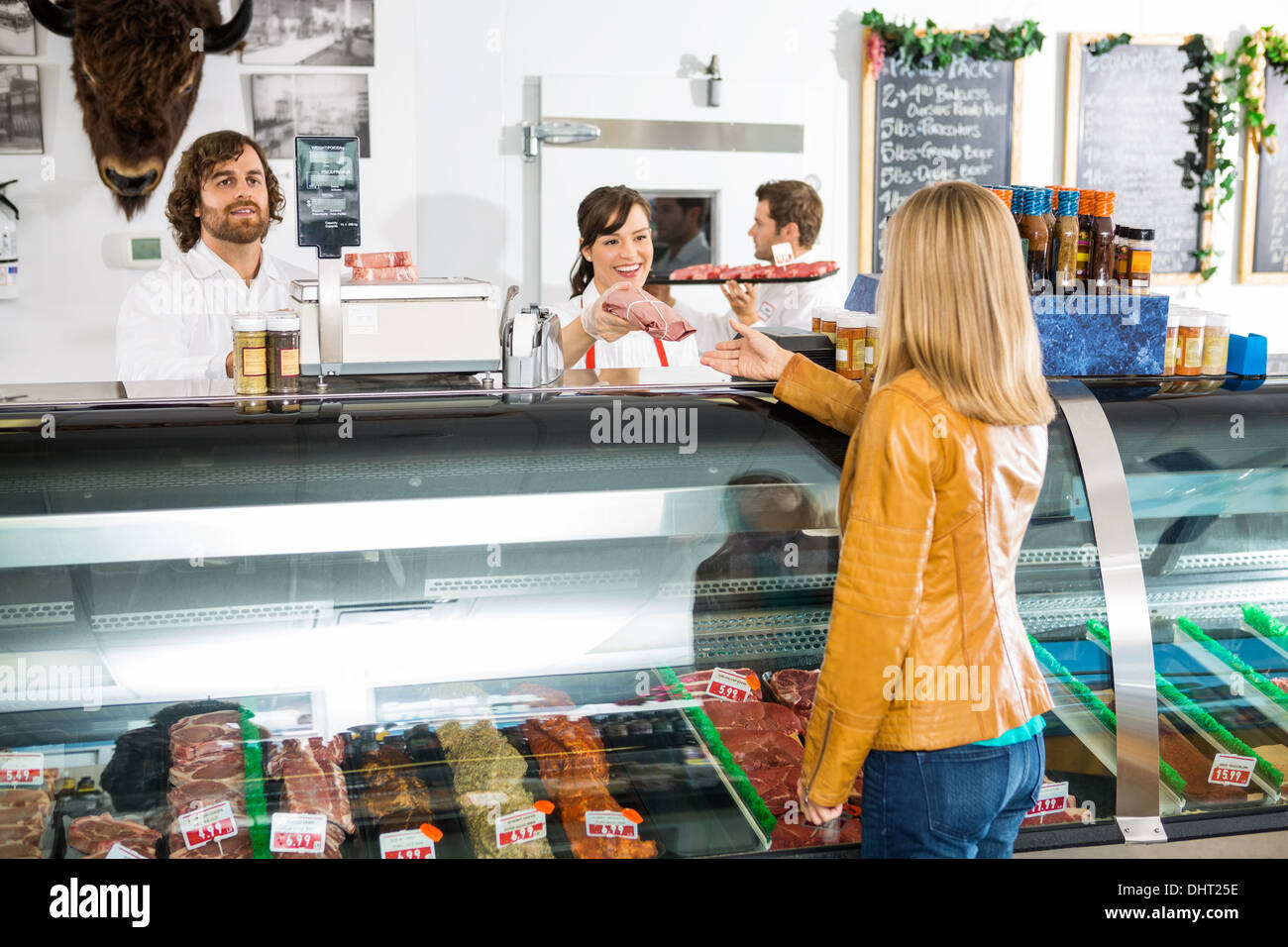 Saleswoman Giving Meat To Female Customer - Stock Image