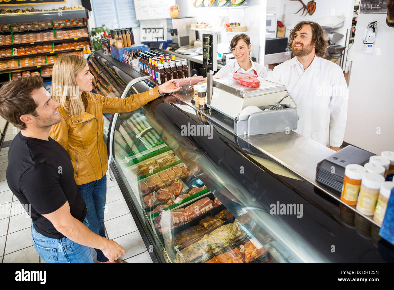 Couple Purchasing Meat From Salesman In Shop - Stock Image