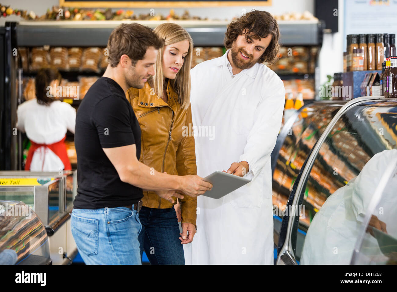 Salesman And Couple Using Digital Tablet At Butcher's Shop - Stock Image