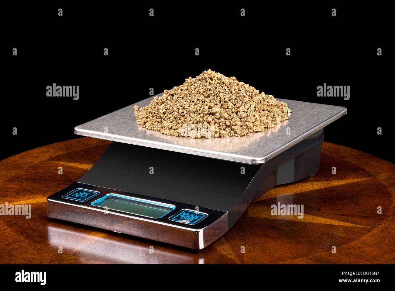 A pile of small gold nuggets on a scale being weighed for their investment value. - Stock Image