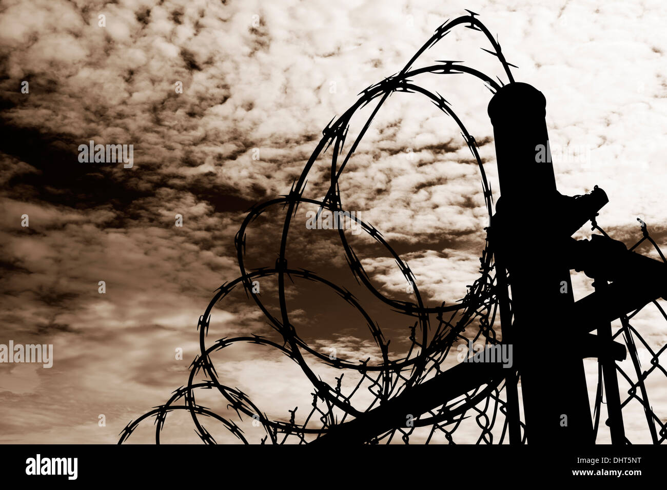 A barbed wire prison fence silhouetted  against a dark, amber moody sky. Stock Photo