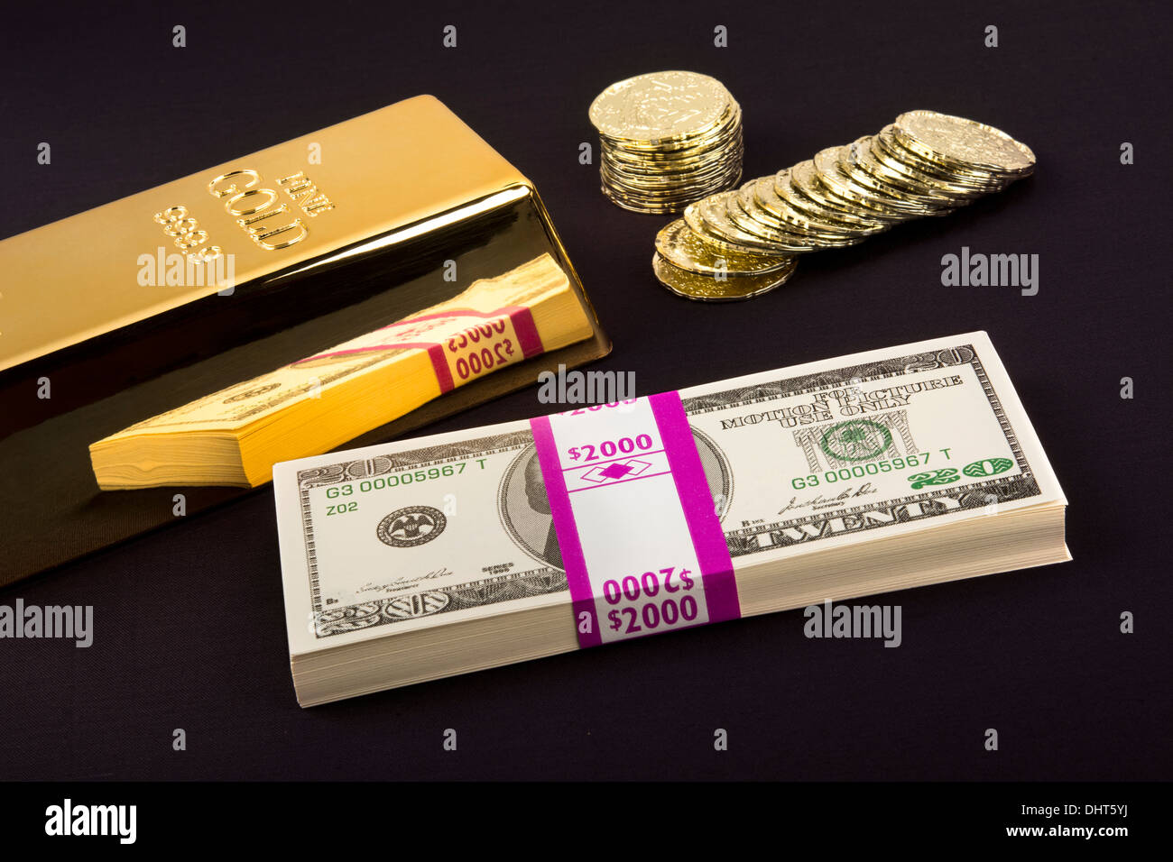Gold coins and a gold bar with a pile of American cash - Stock Image