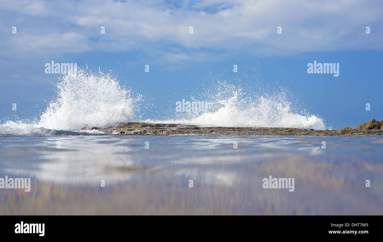 Wave crashing on reef, view from the water surface, Caribbean sea, Costa Rica - Stock Image