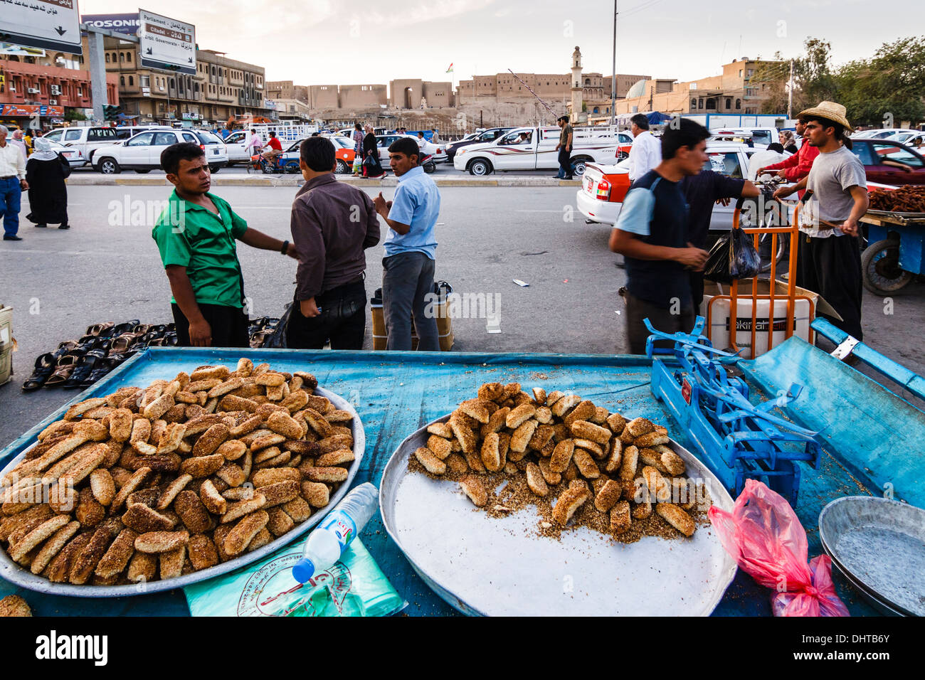 Pastries sold in a street market with citadel in background. Erbil, Iraq - Stock Image
