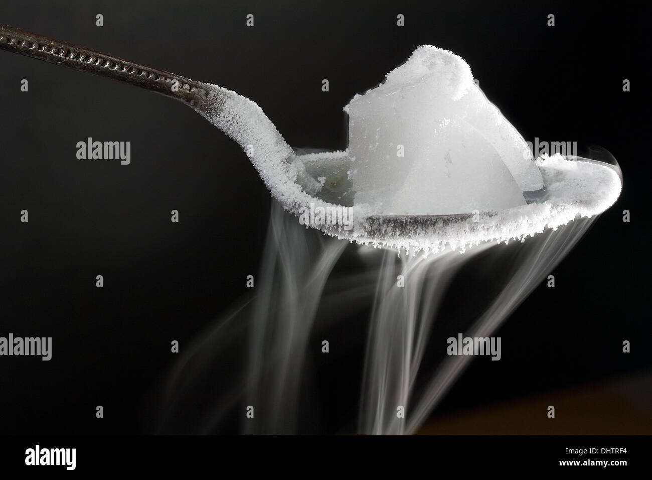 Chunk of Dry Ice (Frozen Carbon Dioxide) on Metal Spoon. Also Shows Water Ice Crystals Forming on the Spoon - Stock Image