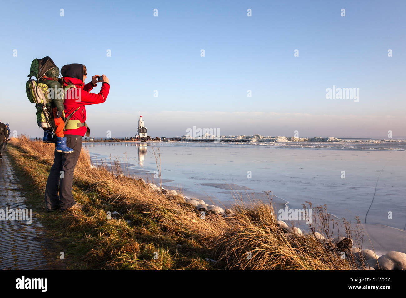 Netherlands, Marken, Ijsselmeer Lake. Winter. Lighthouse called Het Paard. Hiker, woman with child on her back takes picture - Stock Image