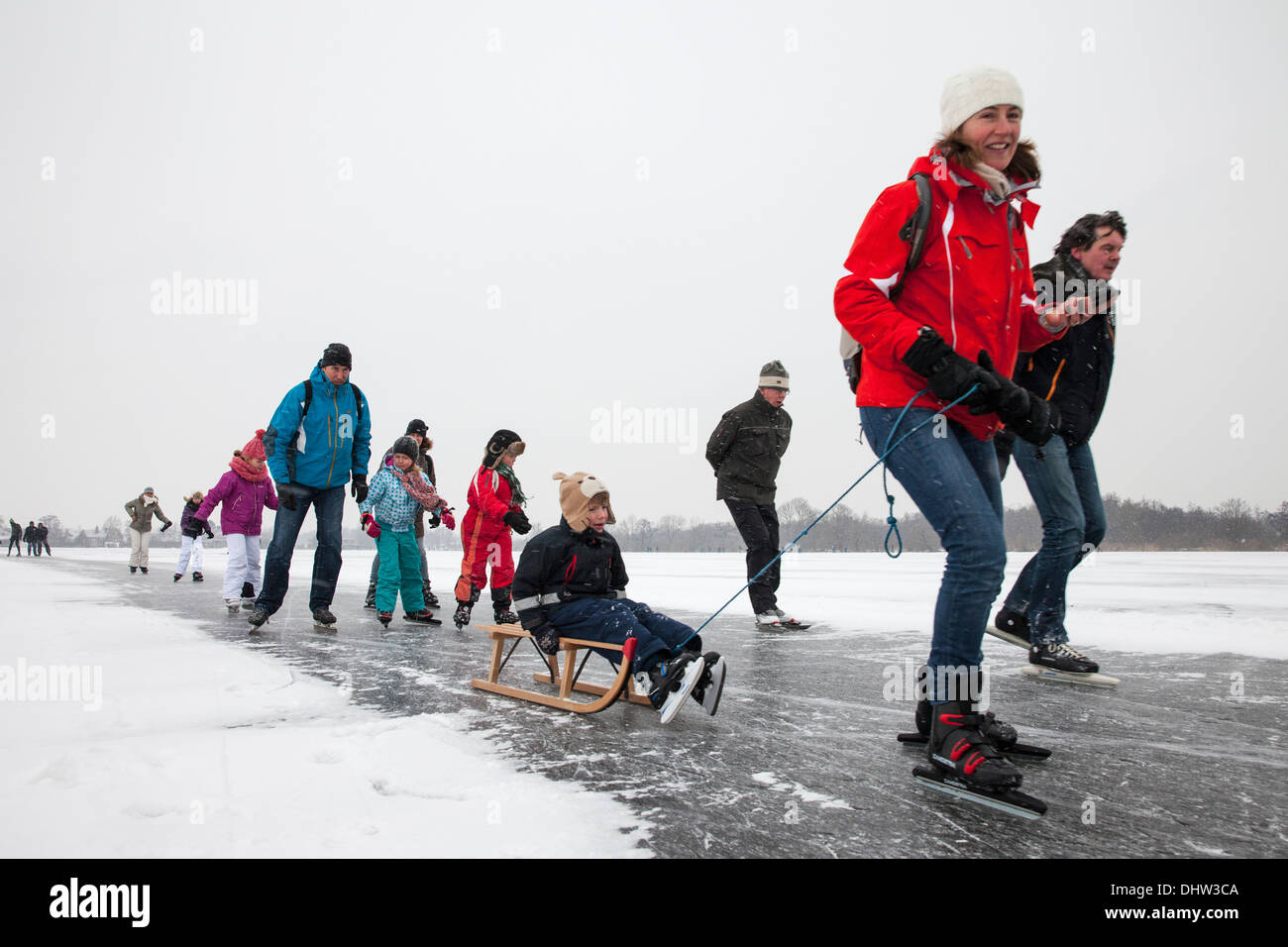 Netherlands, Loosdrecht, Lakes called Loosdrechtse Plassen. Winter. Family ice skating with sledge - Stock Image