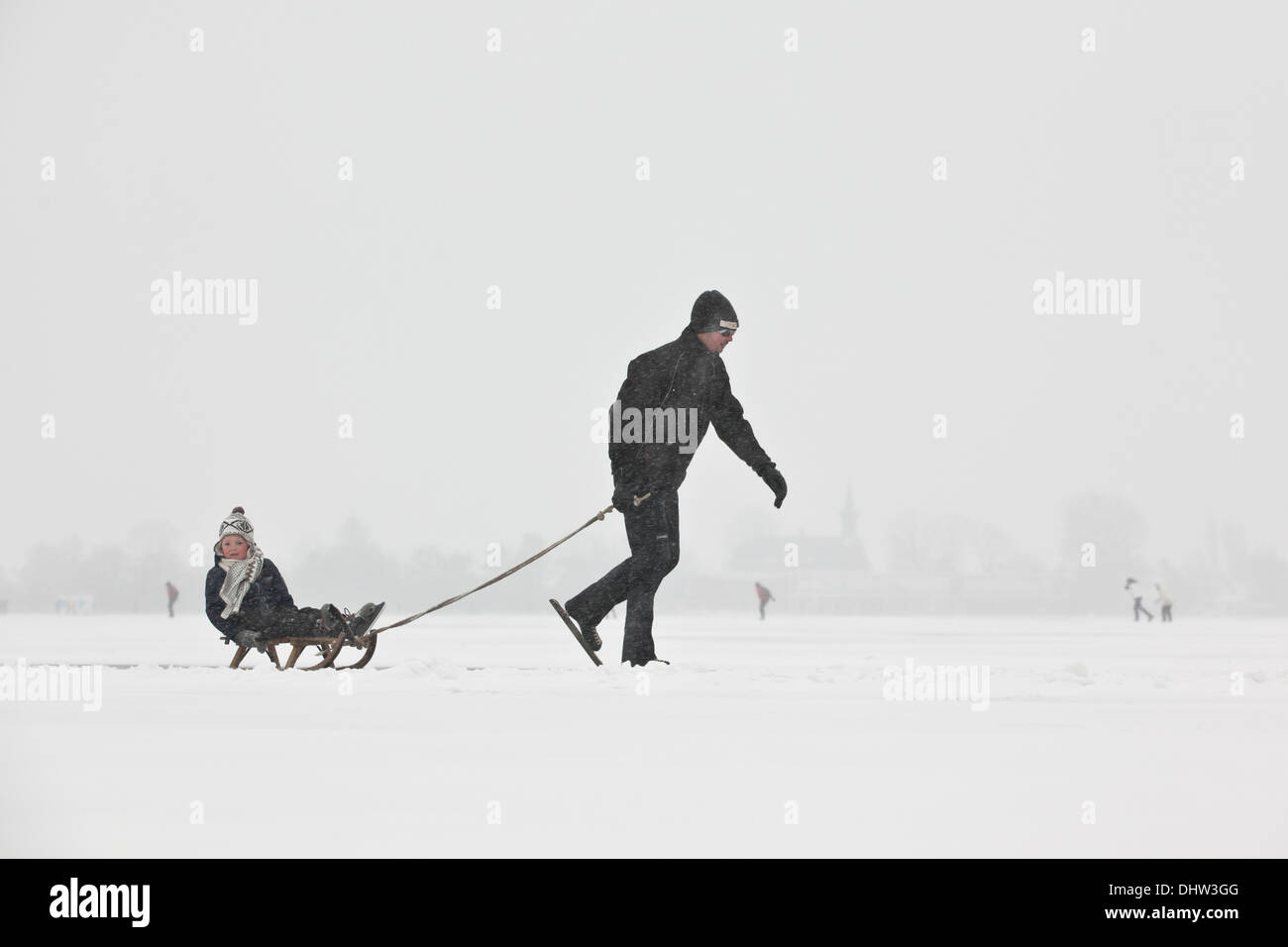 Netherlands, Loosdrecht, Lakes called Loosdrechtse Plassen. Winter. Father ice skating with son on sledge - Stock Image