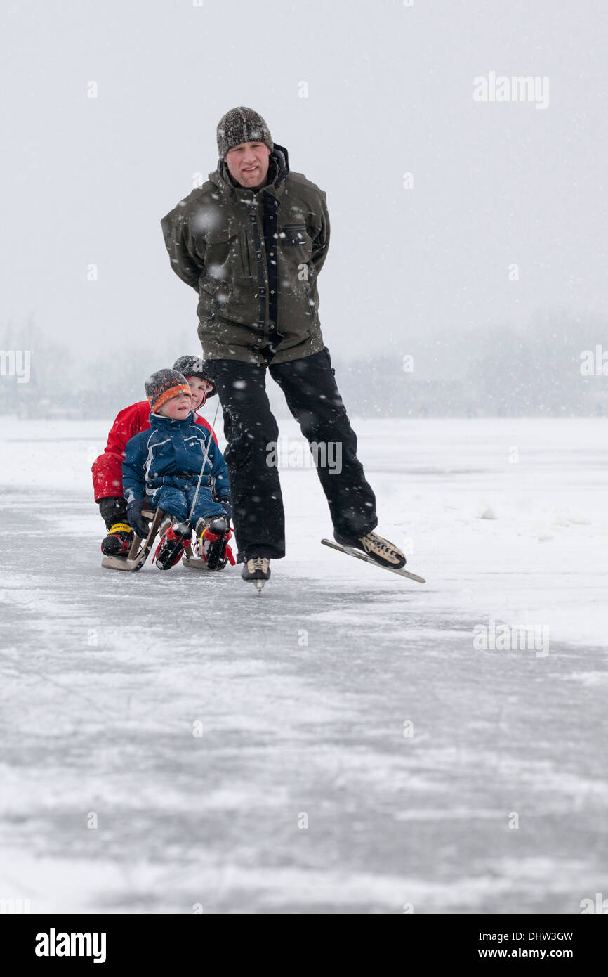 Netherlands, Loosdrecht, Lakes called Loosdrechtse Plassen. Winter. Father ice skating with sons on sledge - Stock Image