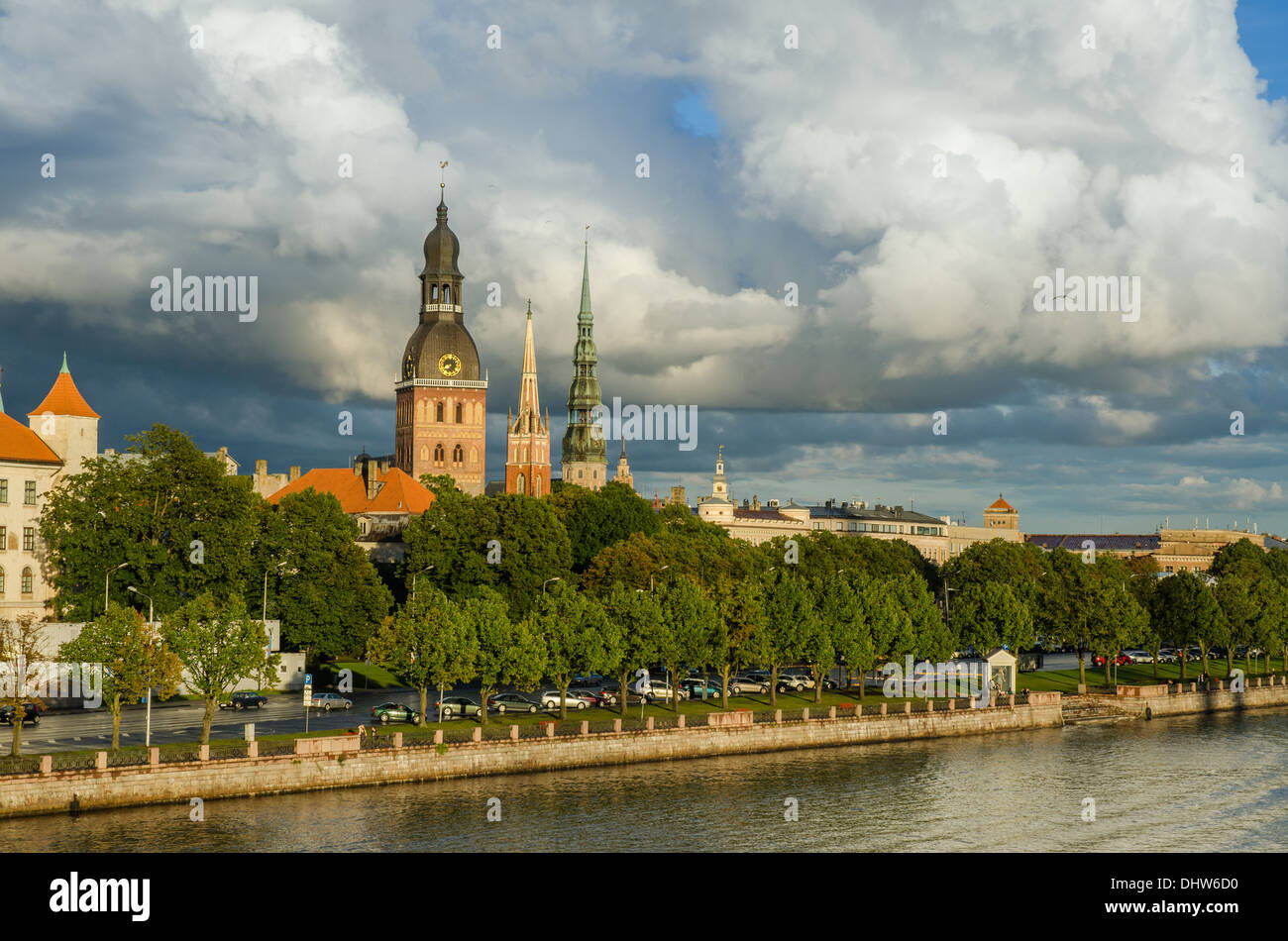 view of the sunset lit cathedral church and st. peter tower of old riga latvia after rain - Stock Image