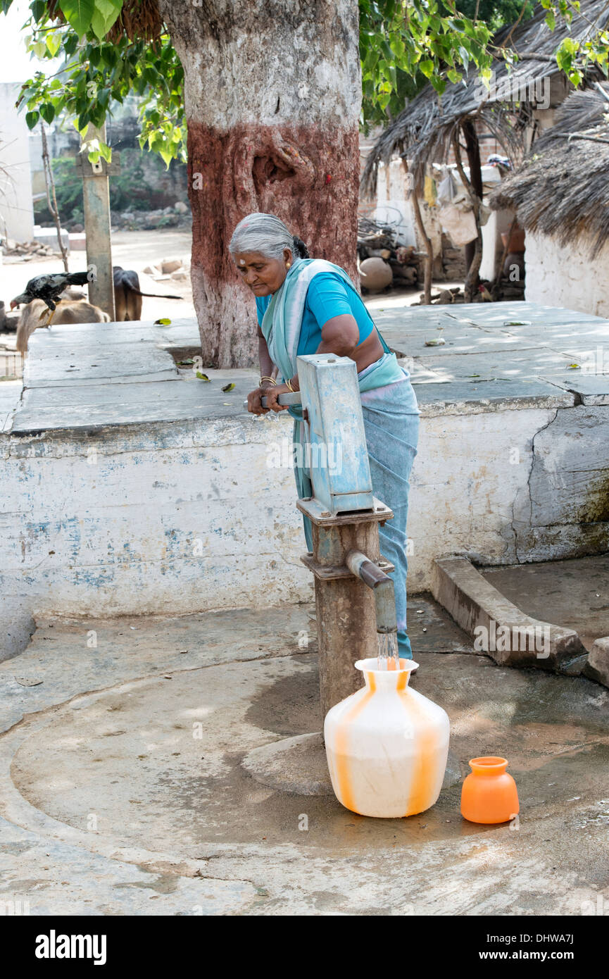 Elderly Indian woman pumping water from a hand pump into a pot in a rural Indian village street. Andhra Pradesh, India - Stock Image