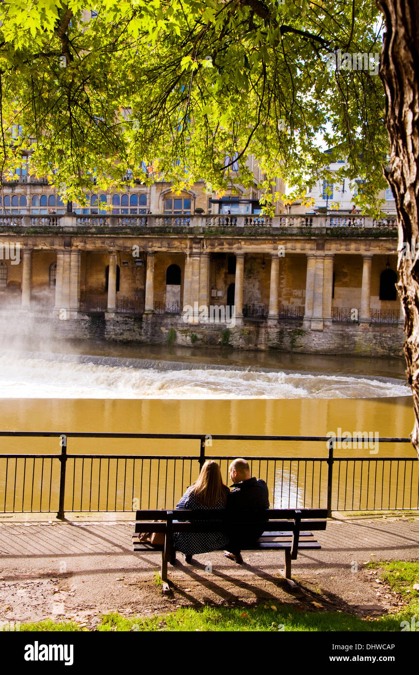 Autumn by the River Avon a couple sit on a bench in Bath Somerset England UK - Stock Image