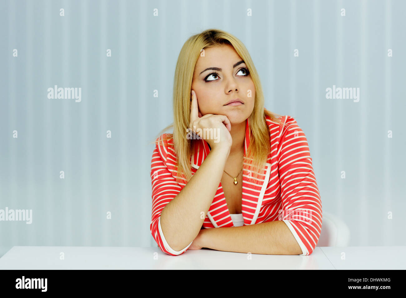 Young thoughtful woman in red jacket sitting at the table in office - Stock Image