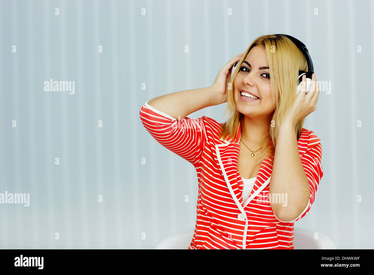 Portrait of a young woman in red jacke listening to music - Stock Image