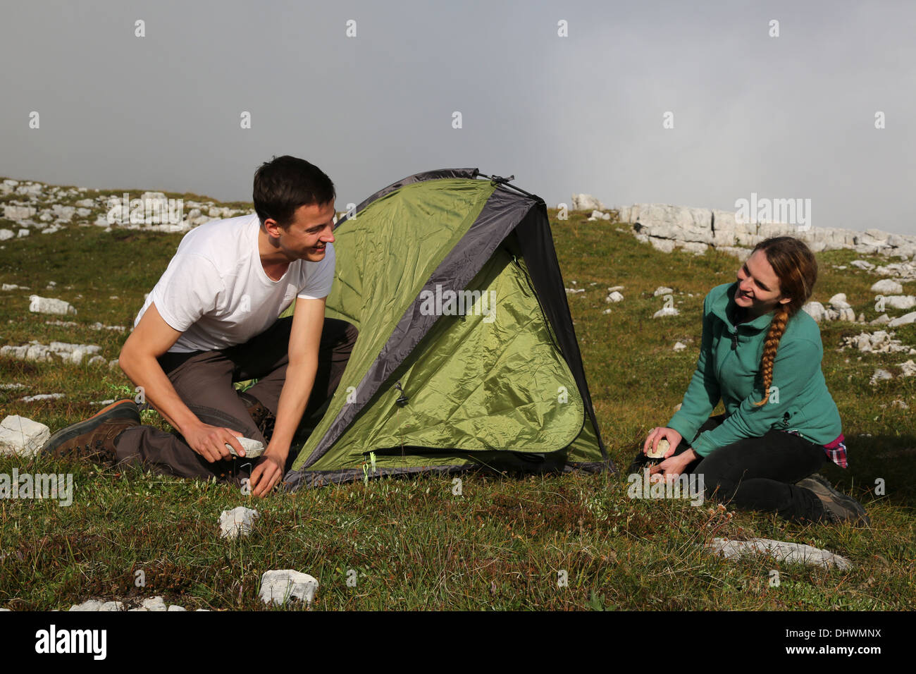 two young people building up a tent in the mountains alps stock