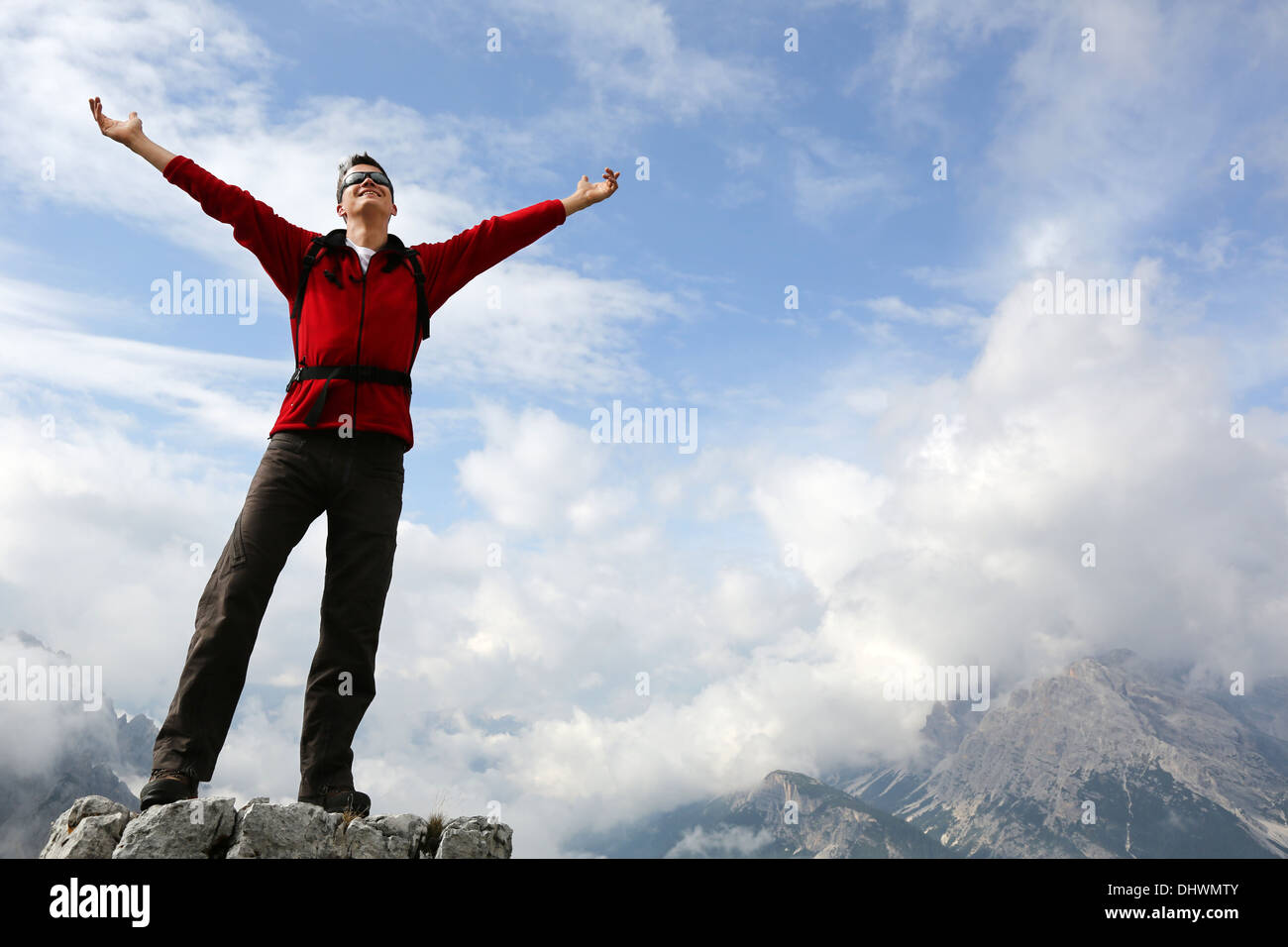Young mountaineer standing on a rock and enjoying freedom in the mountains - Stock Image