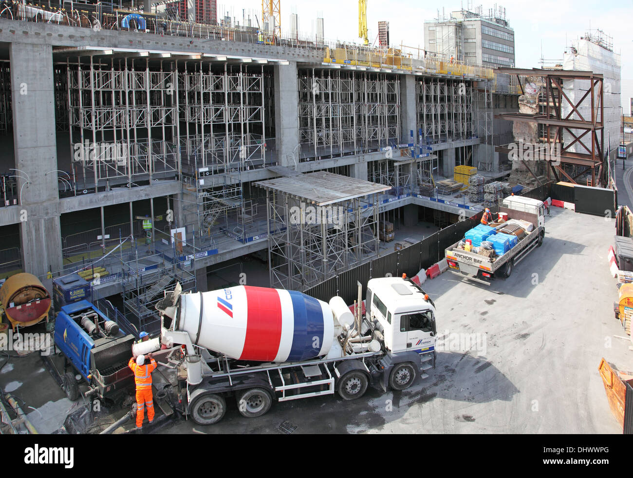 A cement lorry unloads during the construction of a new retail development. Large shoring and formwork is in the background. - Stock Image