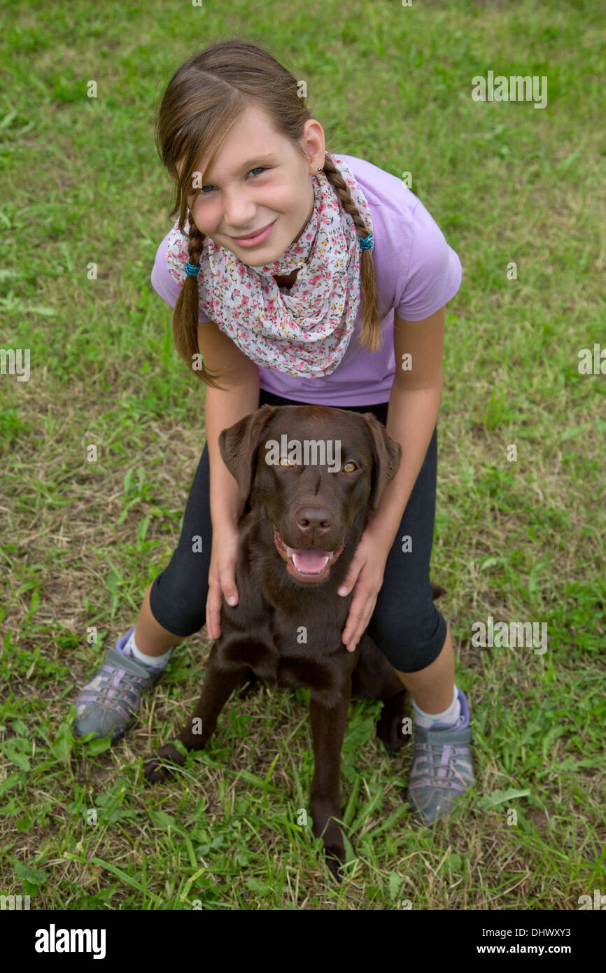 Little girl embracing her dog friend on a meadow Stock Photo