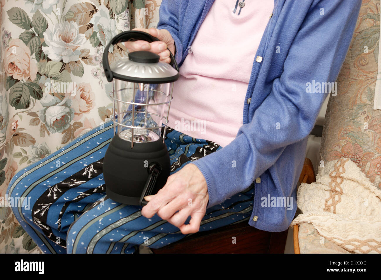 Elderly woman winding up a wind up lantern used as emergency lighting for power cuts power failures & running out of electricity - Stock Image