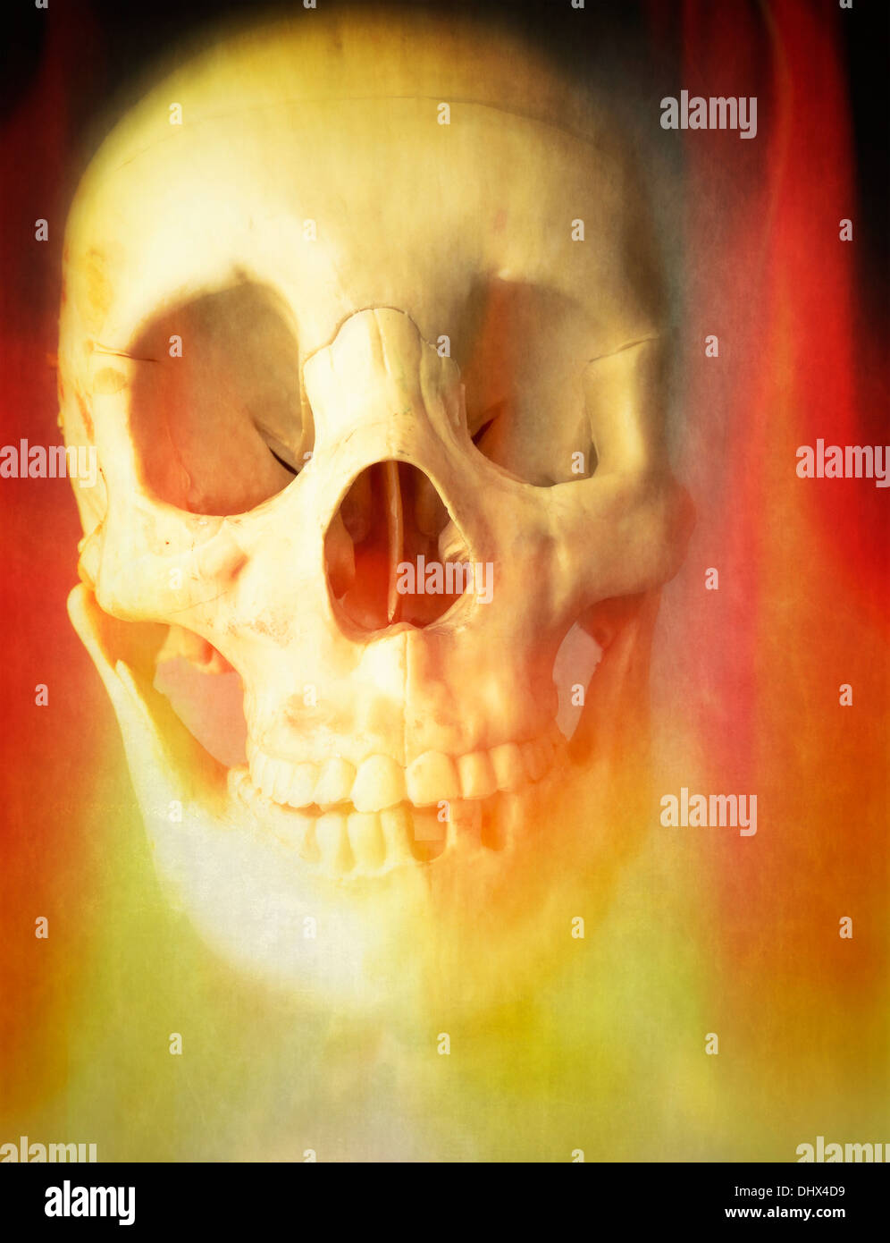 A human skull burning in hell fire. - Stock Image